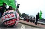 Bola besar yang berisi tuntunan buruh melewati air mancur di depan Monas, Jakarta (1/5). (Foto: Fajrul Islam)