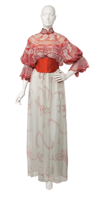 Silk chiffon evening dress worn with a stitched satin obi belt; mandarin collar with frog closures at the back and one decorative frog closure at the front; full sleeves gathered above the elbow forming large frilled cuffs edged with beads; full-length skirt lined in Habotai silk.