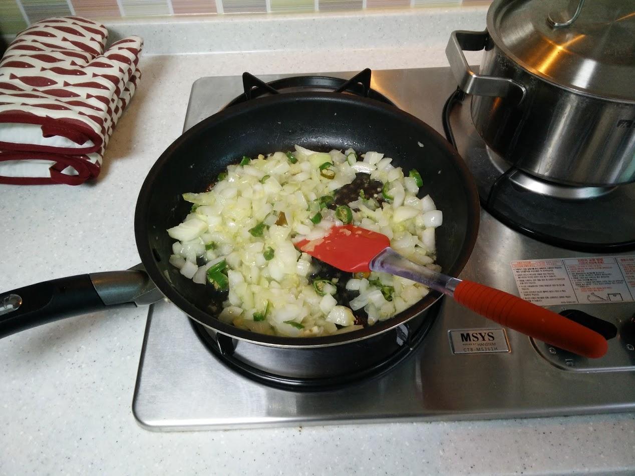 썰어놓은 양파를 다진 마늘과 함께 올리브 오일에 볶습니다. 어느 정도 볶아지면 고추도 투입