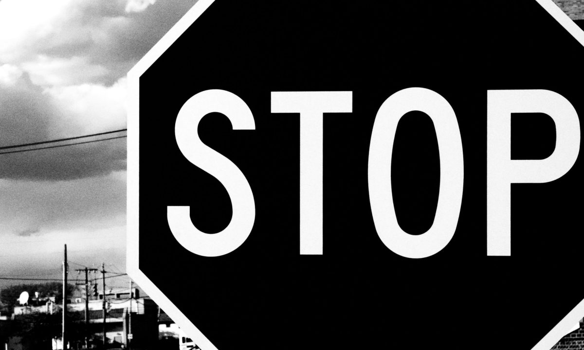 A close up black and white photograph of a stop sign.