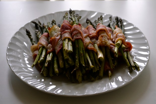 A plate of asparagus wrapped in bacon.  NOM NOM NOM