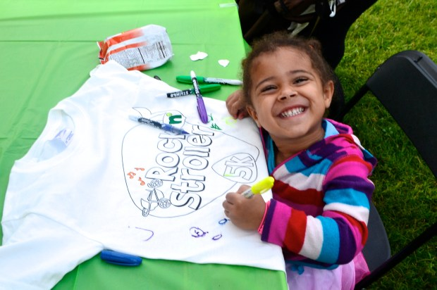 Best fake smile ever.  Coloring in her race t-shirt!