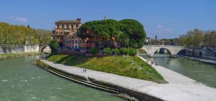 The Isola Tiberina, Rome, from the Ponte Garibaldi Photograph by David Hill, taken 12 April 2015, 14.12 GMT To the left is the Ponte Fabricus, the oldest surviving bridge in Rome, and to the rights is the Ponte Cestio. The latter was rebuilt with three even arches in the 1880s. Beyond it is the campanile of Santa Maria in Cosmedin, with, just to the left, the circular so-called Temple of Vesta, now identified as the Temple of Hercules Victor. Turner's sketches were taken from the left bank of the river for the Ponte Garibaldi was built much later in 1884-88. The new bridge was part of an extensive programme of embankment and flood defences during which the old riverside mills shown in Turner's sketches were removed.