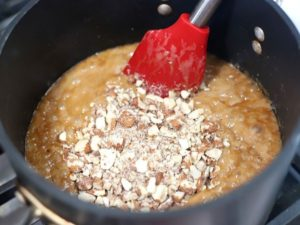 Almond being added to caramel for candy