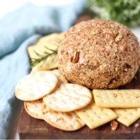 Blue Cheese and Pecan Cheese Ball on a cutting board with crackers.