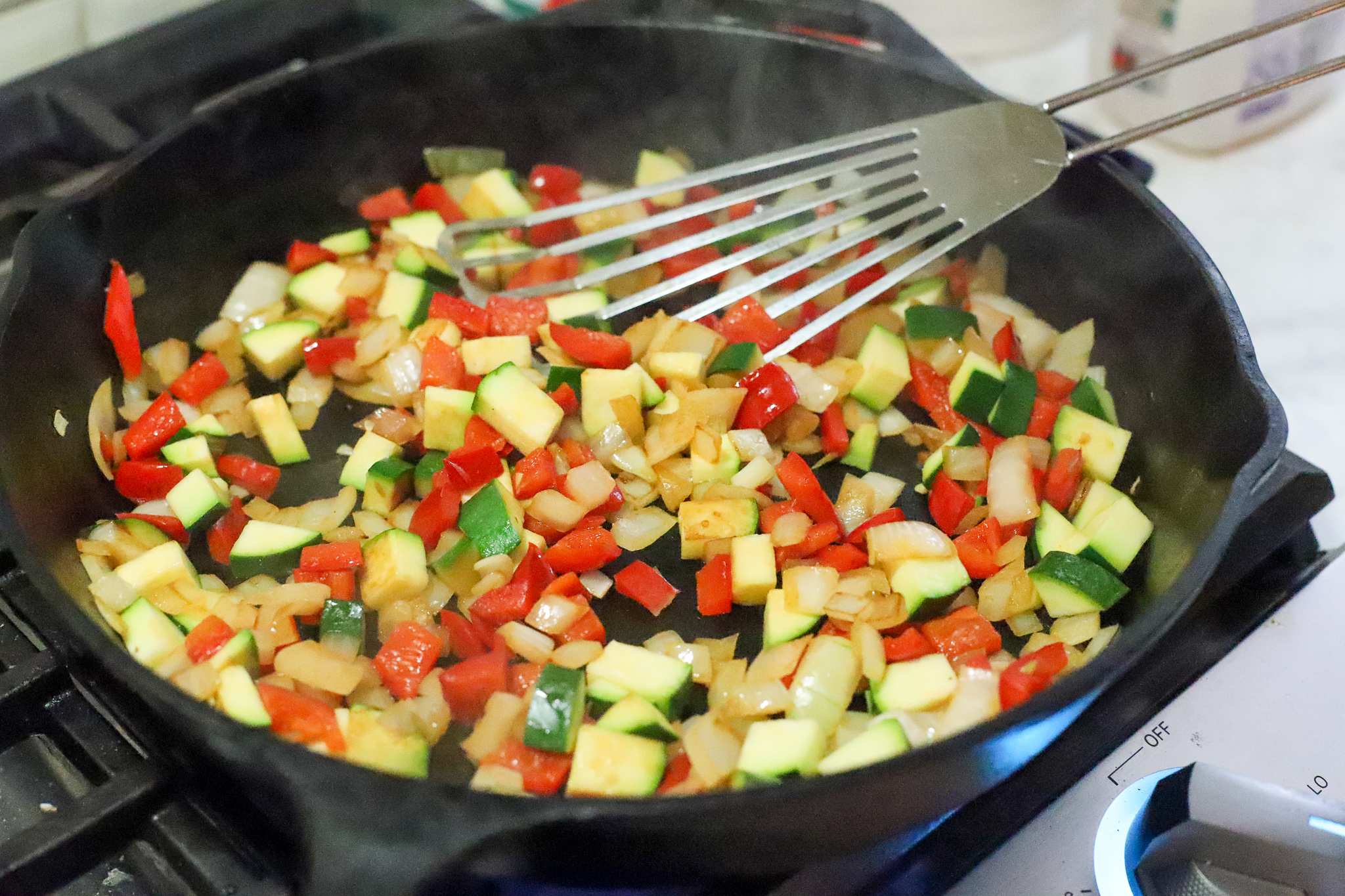 onions, peppers, and zucchini in frying pan