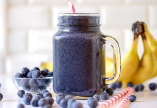 blueberry smoothie in a glass with a straw