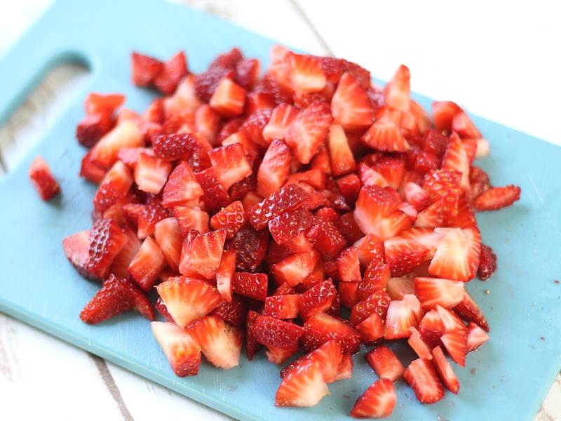 Fresh chopped strawberry on a cutting board.