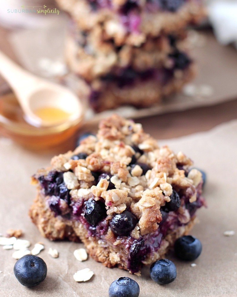 Blueberry Breakfast Bars on the counter with fresh blueberries all around as well as honey in the background.