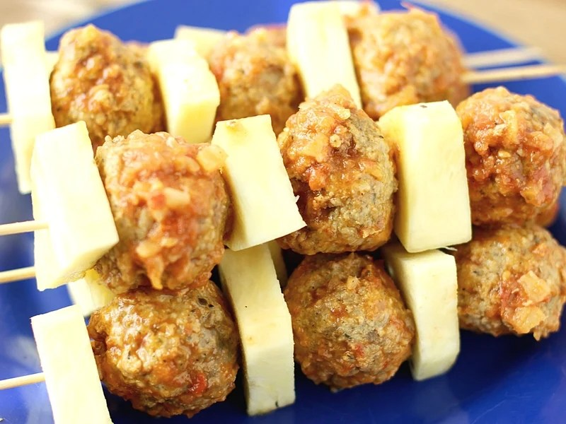 Pineapple and meatballs on a skewer ready to be put on the grill.