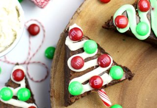 Brownies cut in the shape of Christmas trees with ribbons of frosting and M&M ornaments.