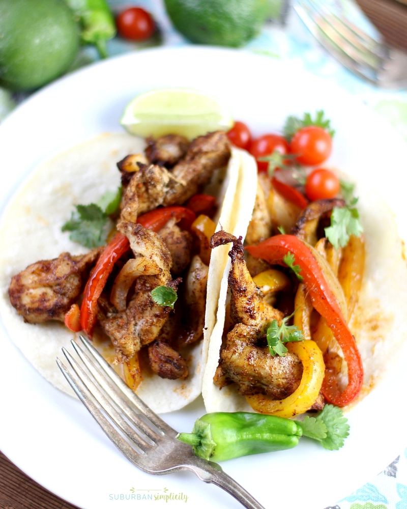 Sheet Pan Chicken Fajitas in a corn tortilla on a white plate topped with cilantro.