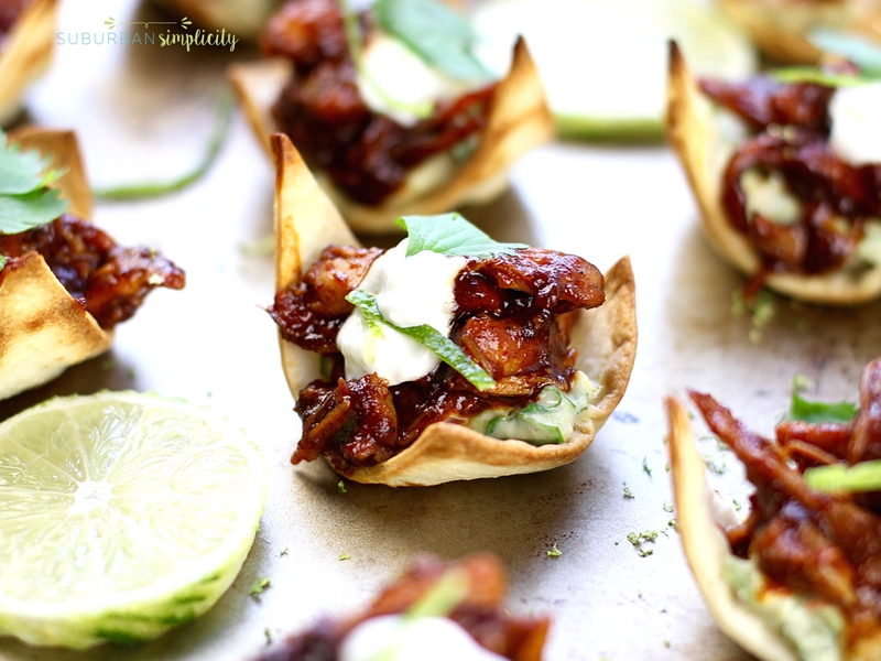 Bite-Sized chipotle chicken tostadas garnished with cilantro and lime on a serving tray.