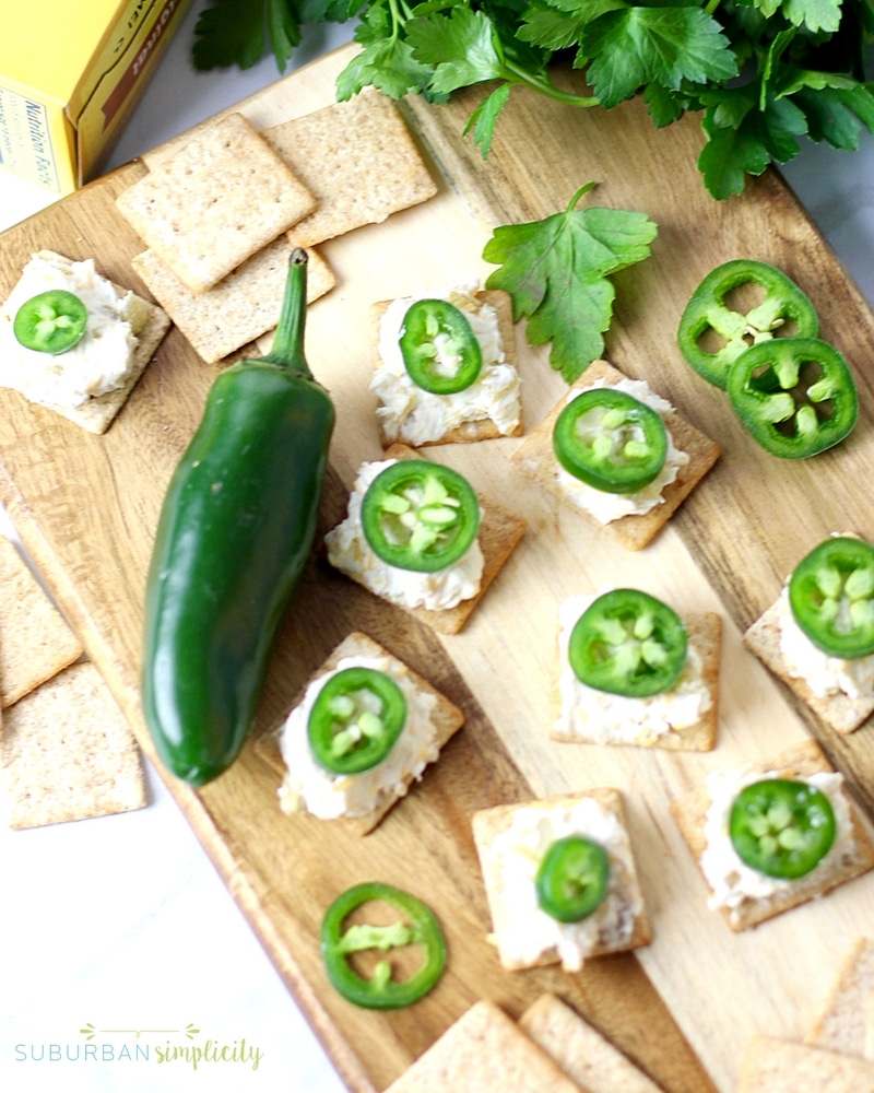 Jalapeno popper toppers on a cutting board with a fresh jalapeño next to them.