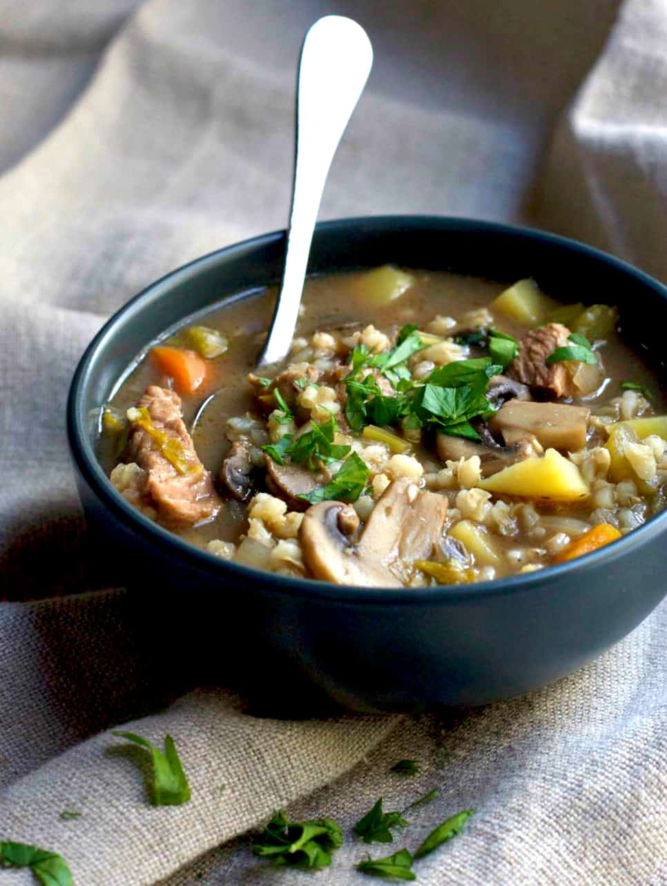Slow Cooker Beef and Barley Soup in a bowl with a spoon sticking out.
