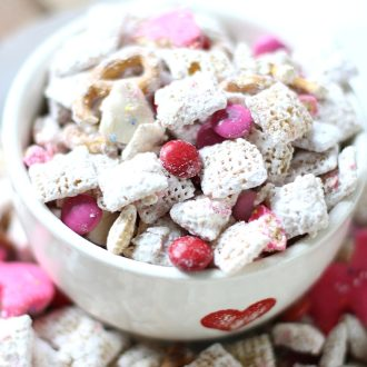 Valentine's Day puppy chow made from chex cereal in a bowl with a heart on it.