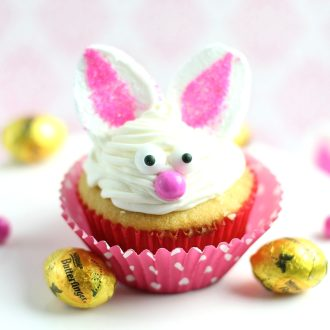 Bunny cupcake in a pink wrapper and Butterfinger candies next to it.