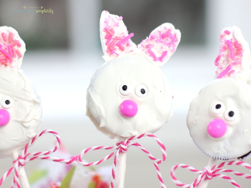 Three Easter Oreo Cookie Pops with a ribbon around their lollipop sticks.
