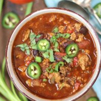 Healthy Crockpot Turkey Chili with jalapeño and green onion garnish