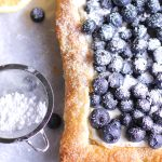 Blueberry tart with powdered sugar dusted on top.