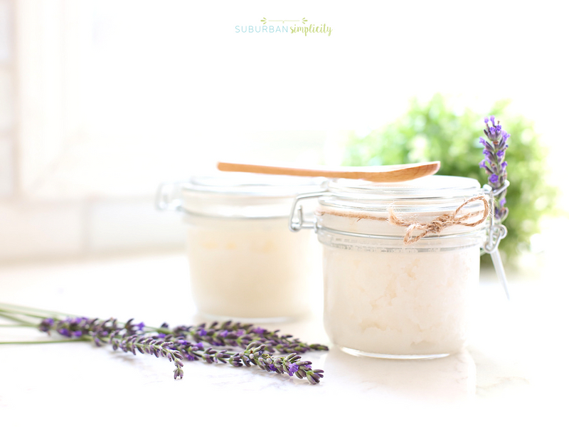 Lavender sugar scrub in jars with fresh lavender next to it.