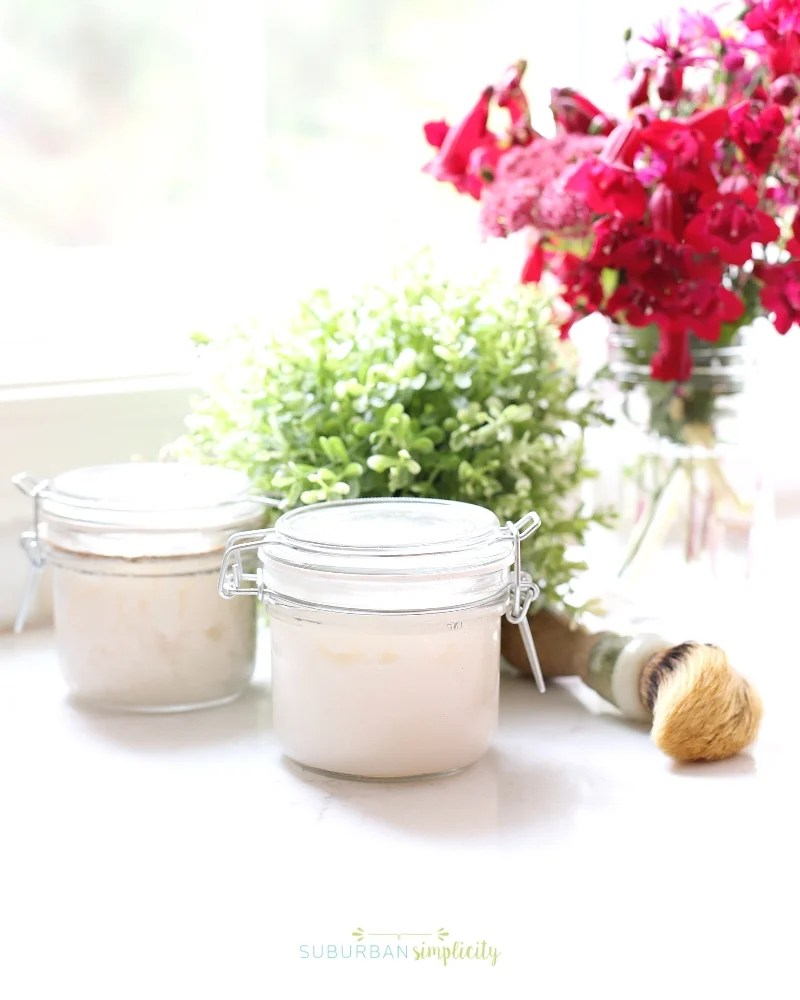 Jar of body scrub on the counter with flowers in the background.