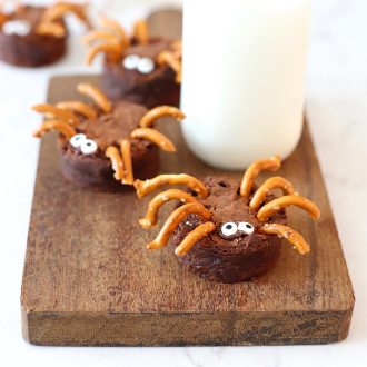 Brownie Spiders on a cutting board with milk.