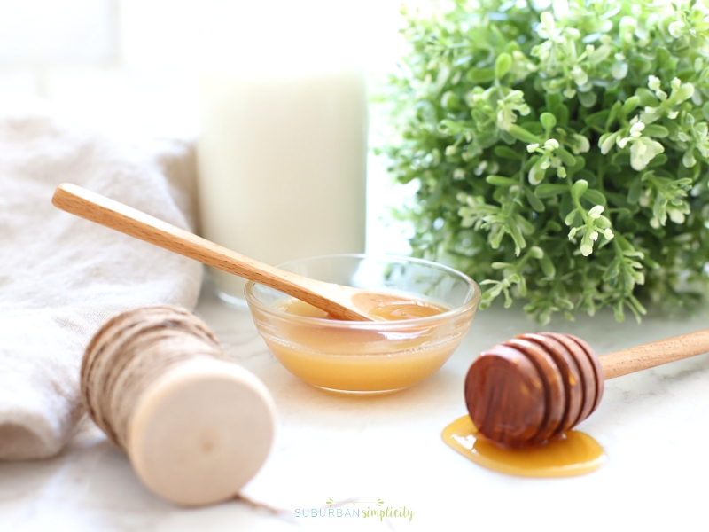 Milk and honey sugar scrub with a wooden spoon in it.
