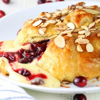 A close up of food on a plate, with Brie and Cherries