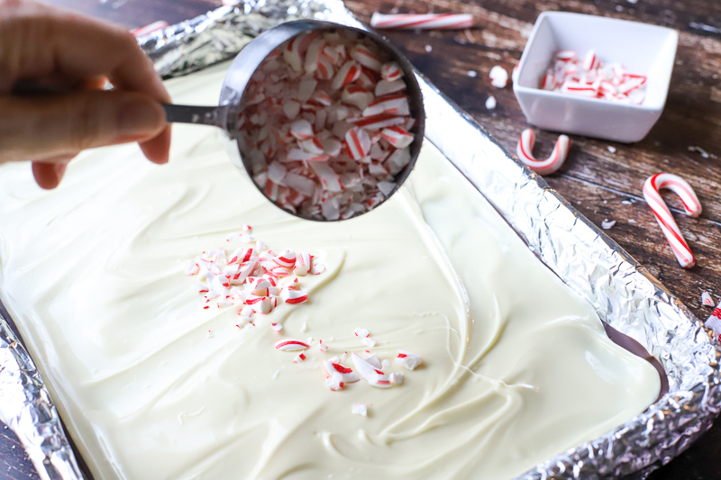 Candy canes being spread on peppermint bark.