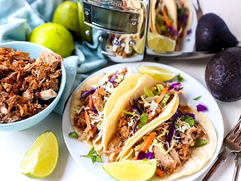 Crockpot Pulled Pork Tacos in front of a slow cooker.