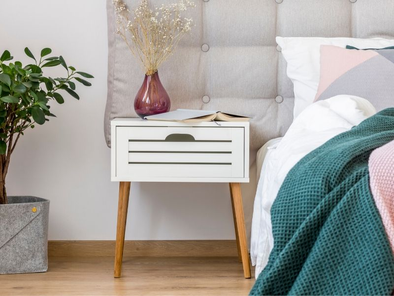 nightstand next to a made bed