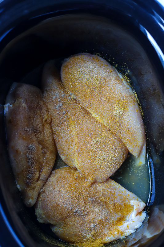 A close up of seasoned Chicken in a Crock Pot