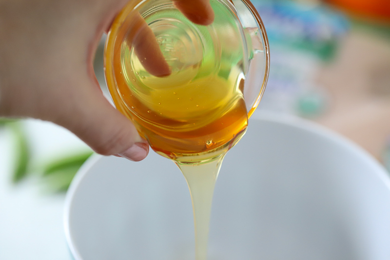 honey being poured into a bowl for Asian chicken