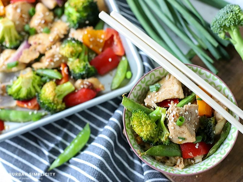 Bowl of sesame chicken and vegetables with chopsticks