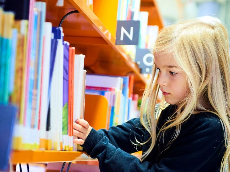 child picking books at the library