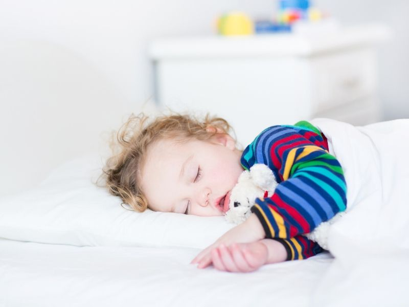 Toddler sleeping in bed.