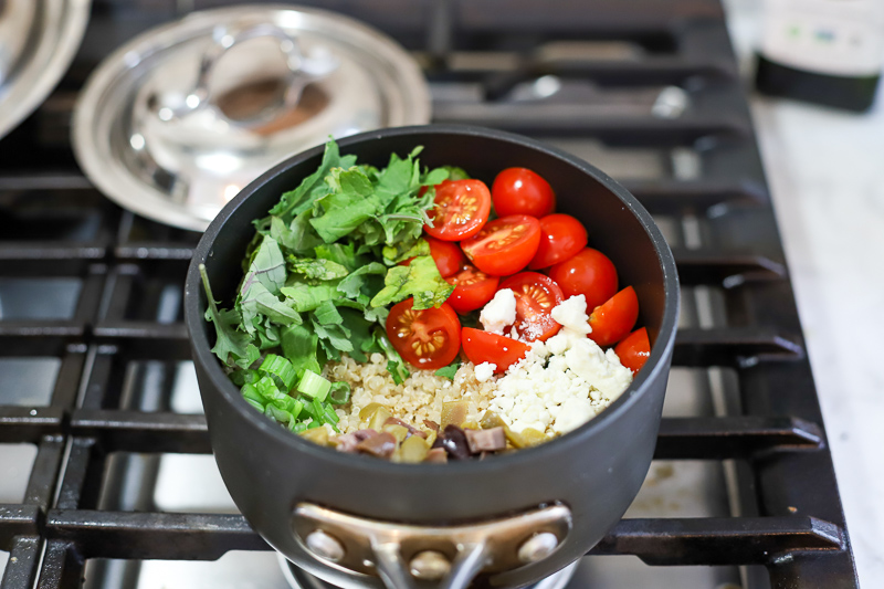 Quinoa, tomatoes, feta cheese, and olives in a pot