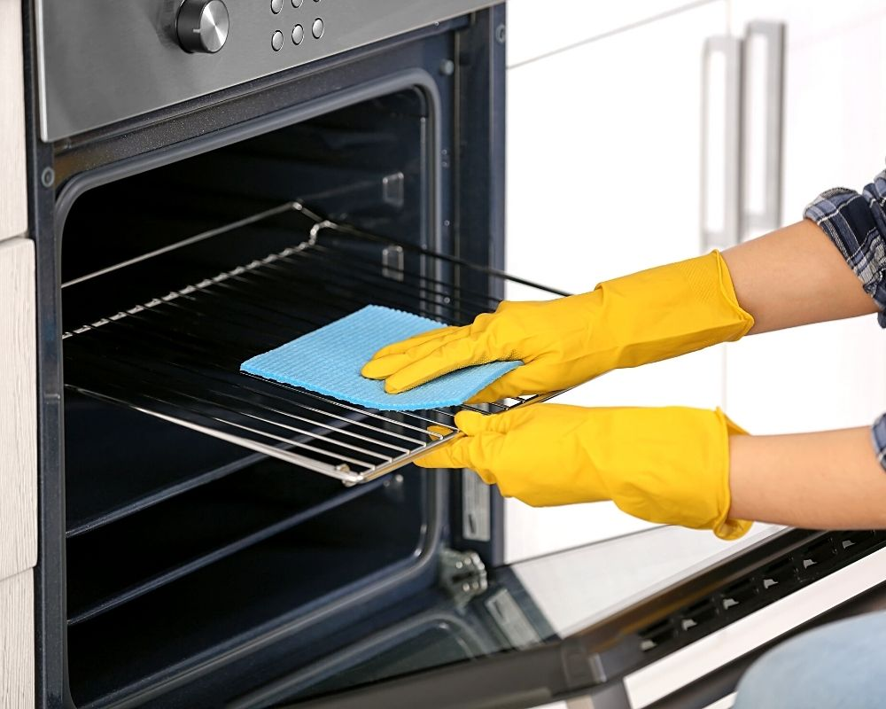 someone cleaning an oven with rubber gloves