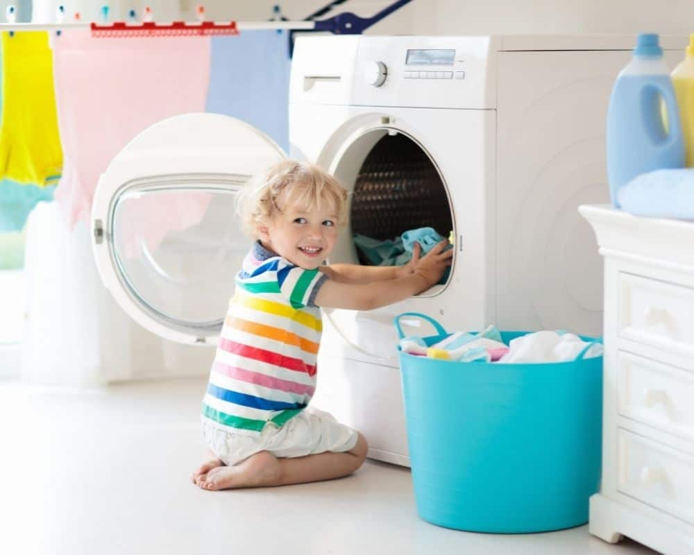toddler in front of washing machine