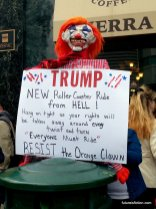 """Clown puppet with sign: """"TRUMP: New roller coaster ride from HELL! Hang on tight as your rights are stripped away at every twist and turn. Everyone must ride!"""""""