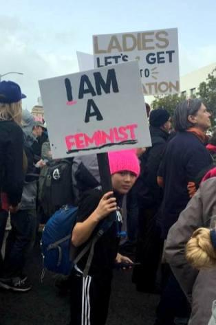 boy holding I am a feminst protest sign