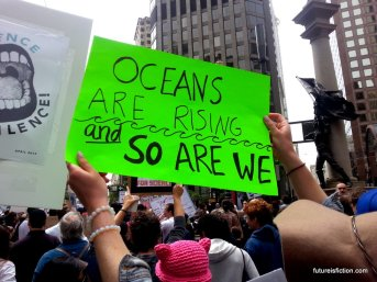 """Oceans are rising and so are we"" protest sign"