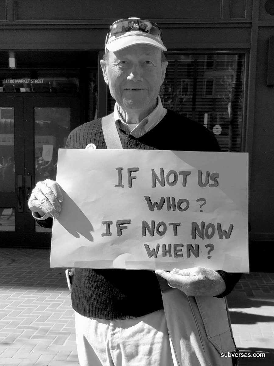 "Man with sign: ""If not us who? If not now when?"""