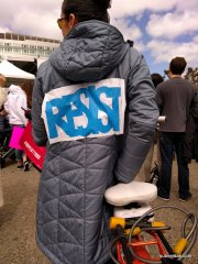 Bicyclist with jacket that says RESIST in bold blue letters.