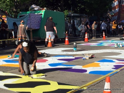 artists painting mural that can be seen from the sky