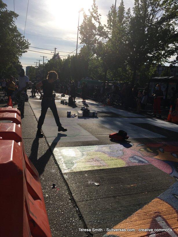 artist painting huge BLM mural at dusk
