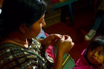 Pequeña aprendiz de araña en Pantelho. Las mujeres muchas veces cuidan y alimentan a sus niños mientras tejen.