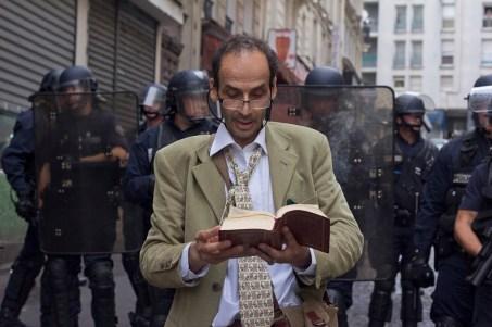Manifestante lee texto sagrado frente a la valla de riots , segundos antes de ser atacado por la policía.