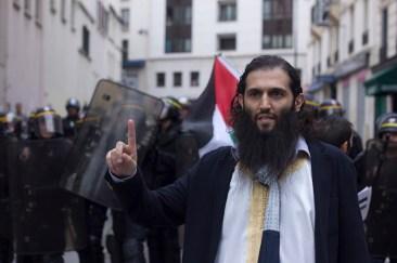 Manifestante proclama un discurso pro-Palestina frente a la valla de Riots.